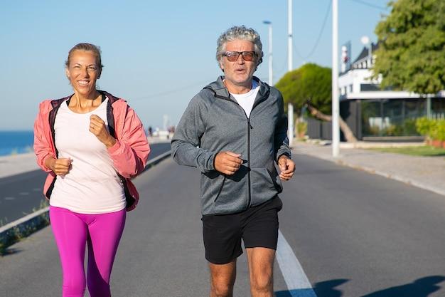 Fröhliches reifes paar, das entlang flussufer läuft. grauhaariger mann und frau, die sportkleidung tragen und draußen joggen. aktiver lebensstil und alterskonzept
