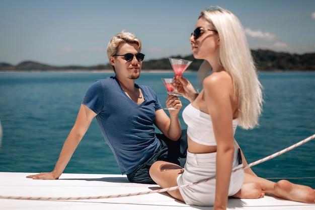 Fröhliches reizendes junges aktives paar mit blondem haar, das spaß im freien hat und cocktails in kristallgläsern hält.