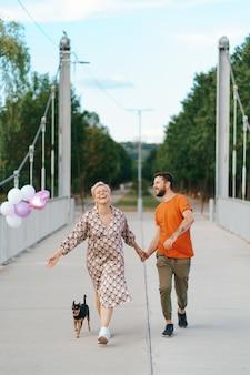 Fröhliches reizendes paar, das glücklich auf brücke mit ihrem hund und den lächelnden rosa luftballons geht