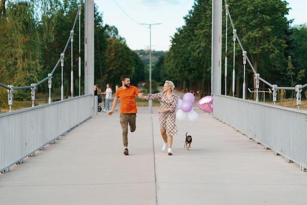 Fröhliches reizendes paar, das glücklich auf brücke mit ihrem lächelnden hund und den rosa luftballons läuft