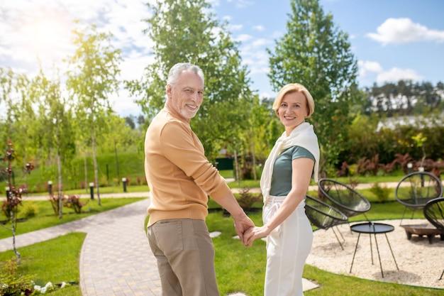 Fröhliches romantisches paar, das auf dem gefliesten fußweg steht