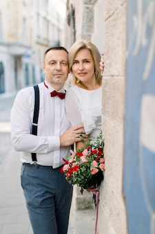 Fröhliches romantisches paar mittleren alters, gutaussehender mann in eleganter kleidung und hübsche dame in weißem kleid und blumenstrauß, posiert mit blick auf die kamera in der nähe des alten stadtgebäudes