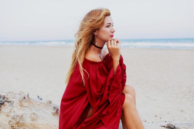 Fröhliches rothaariges mädchen, das am strand aufwirft. auf weißem sand sitzen. windige haare. trendiges outfit. lebensstilporträt. reisestimmung. ozeanküste.