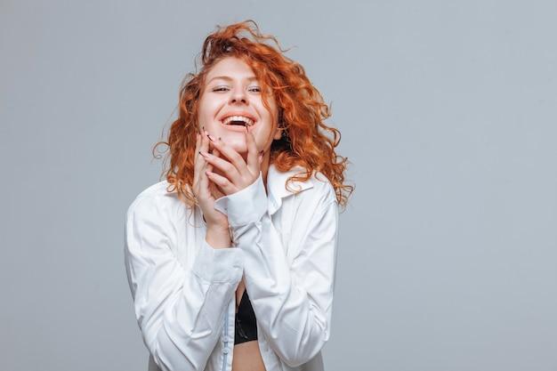 Fröhliches rothaariges mädchen, das in schwarzen dessous und weißem hemd lacht