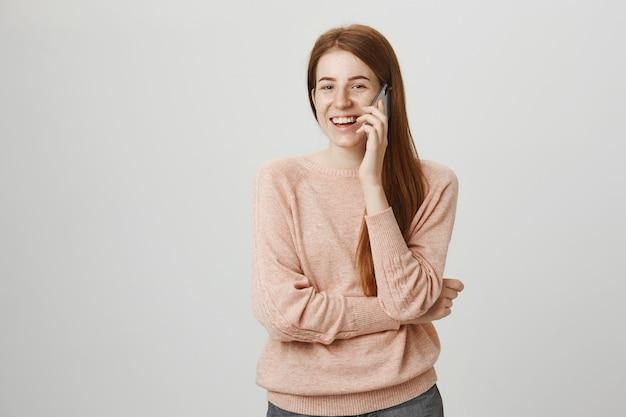Fröhliches rothaariges mädchen, das mobiles gespräch hat und lächelt