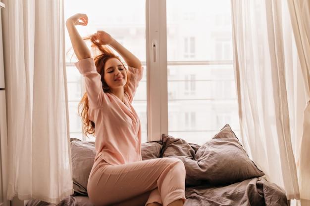 Fröhliches rothaariges mädchen im pyjama, das am morgen lächelt. fröhliche ingwerfrau, die im bett aufwirft.