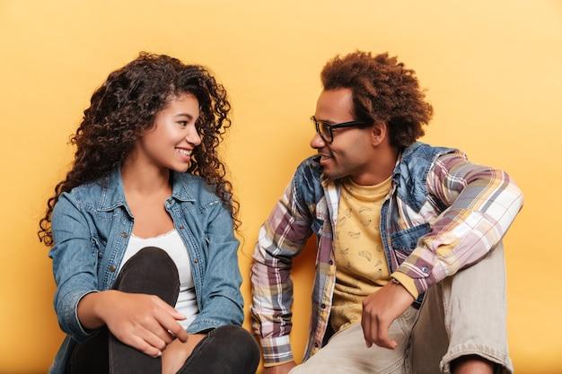 Fröhliches, schönes afroamerikanisches junges paar, das auf gelbem hintergrund sitzt und sich ansieht