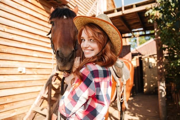Fröhliches schönes junges frauengowgirl mit ihrem pferd auf ranch