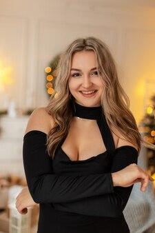 Fröhliches, schönes junges mädchen mit einem natürlichen lächeln in einem trendigen, eleganten schwarzen kleid auf einem hintergrund von weihnachtsbeleuchtung und dekoration zu hause. winterferien