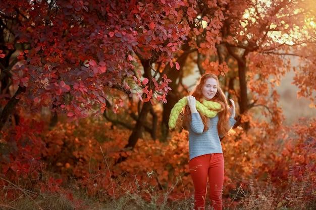 Fröhliches schönes junges mädchen steht im wald in einem warmen schal auf ihren schultern