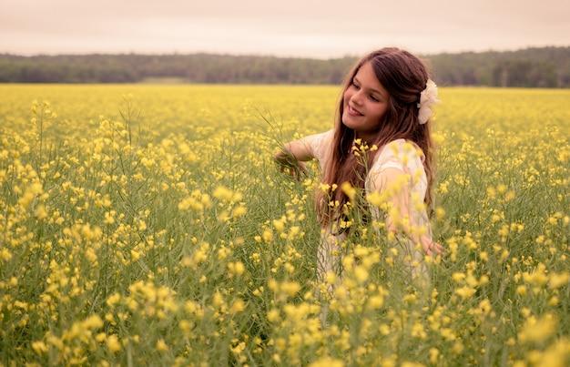 Fröhliches schönes kind, das in einem feld der gelben blumen geht und natur genießt
