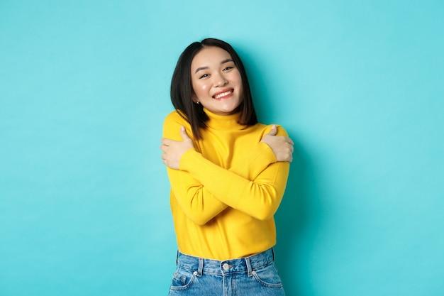 Fröhliches schönes mädchen, das seinen eigenen körper umarmt, sich lächelt und kuschelt und sorglos in gelbem pullover vor blauem hintergrund steht