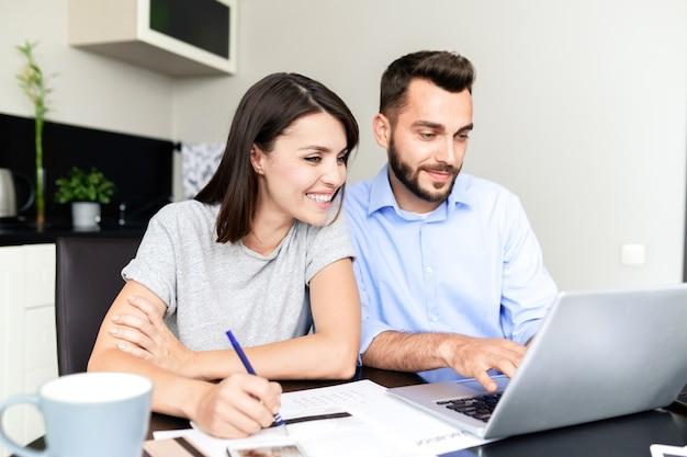 Fröhliches schönes paar, das am tisch sitzt und laptop beim ausfüllen des steuererklärungsformulars auf der website verwendet