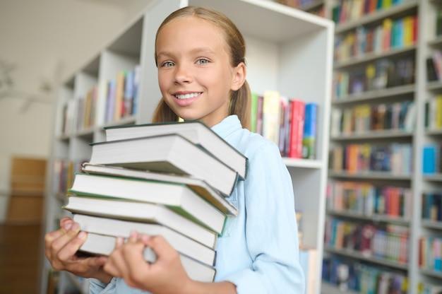 Fröhliches schulkind mit lehrbüchern in der bibliothek stehen