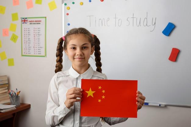 Fröhliches schulmädchen, das flagge von china im klassenzimmer zeigt