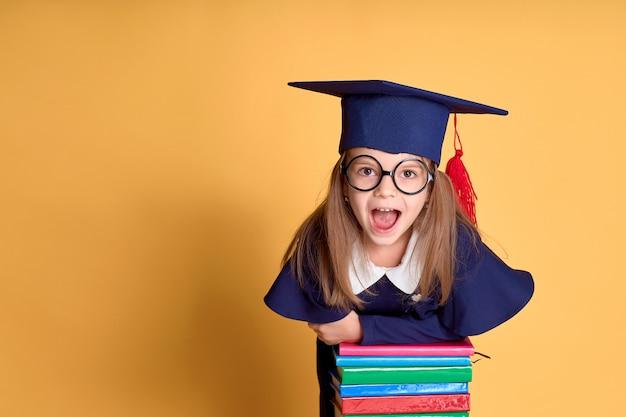 Fröhliches schulmädchen im abschlussoutfit lächelnd, während auf stapel von lehrbüchern gelehnt