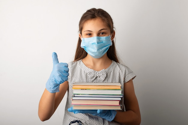 Fröhliches schulmädchen in der medizinischen schutzmaske und in den handschuhen, die mit büchern stehen