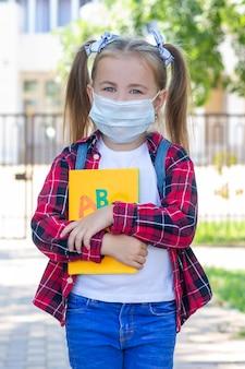 Fröhliches schulmädchen in einer schutzmaske mit rucksack und einem lehrbuch in den händen. in einem weißen t-shirt und einem karierten hemd. vertikales foto