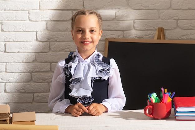 Fröhliches schulmädchen-lesebuch im klassenzimmer in der schule. kinder im klassenzimmer in der schule. erste klasse.