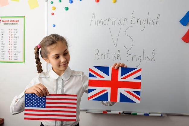 Fröhliches schulmädchen mit amerikanischen und britischen flaggen im klassenzimmer, das unterschiede in den arten der englischen sprachen lernt
