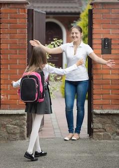 Fröhliches schulmädchen rennt zu ihrer mutter und wartet nach der schule auf sie