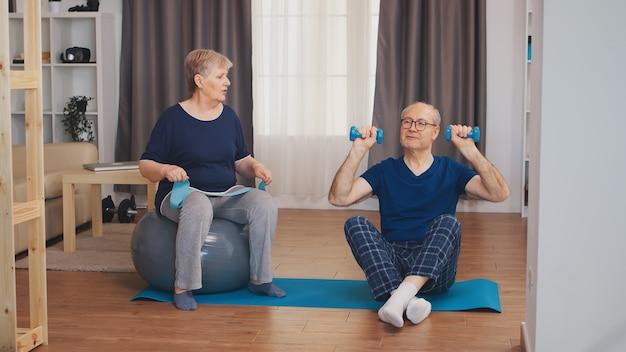 Fröhliches seniorenpaar, das zusammen auf yogamatte trainiert. gesunder lebensstil für alte menschen zu hause, training und training, sportliche aktivität zu hause