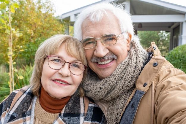 Fröhliches seniorenpaar in stilvoller warmer freizeitkleidung, das sie mit einem lächeln ansieht, während es vor der kamera gegen garten und landhaus steht