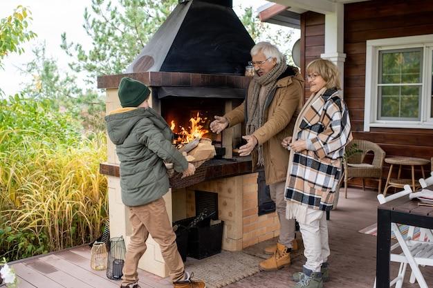 Fröhliches seniorenpaar in warmer freizeitkleidung, das am kamin ihres landhauses steht und enkel mit brennholzkiste trägt