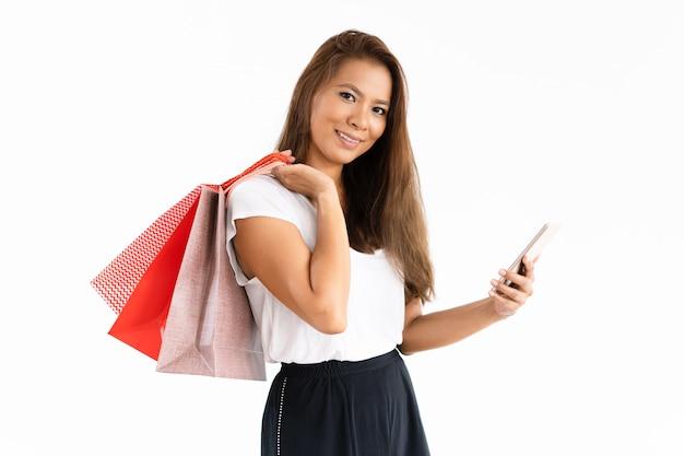 Fröhliches shopaholic, das mit der mobilen app bezahlt