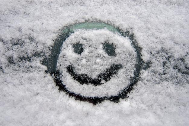 Fröhliches smiley-gesicht auf der schneebedeckten windschutzscheibe eines autos im winter