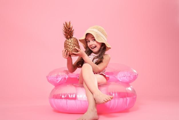 Fröhliches sommermädchen mit ananas auf farbigem hintergrund