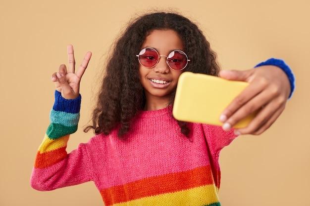 Fröhliches stilvolles mädchen, das selfie auf smartphone nimmt