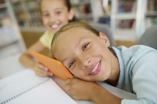 Fröhliches süßes blondes schulmädchen mit einem tablet-computer und ihrem zufriedenen dunkelhaarigen freund, der in die kamera lächelt