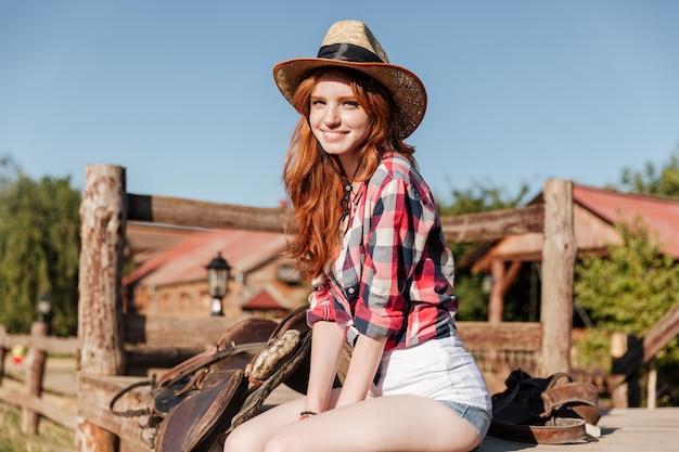 Fröhliches süßes rothaariges cowgirl, das auf dem ranchzaun sitzt und sich ausruht