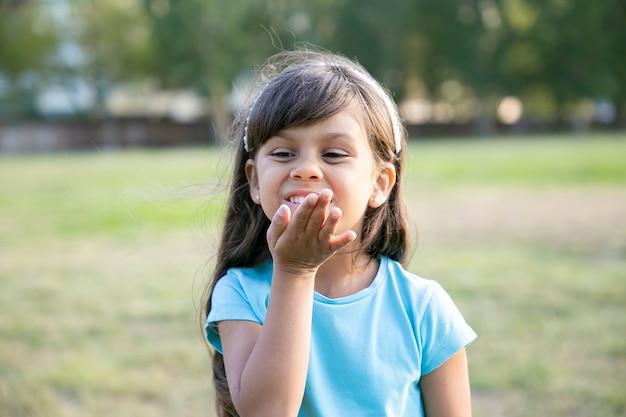 Fröhliches süßes schwarzhaariges mädchen, das luftkuss sendet, im park aufwirft, wegschaut und lächelt. konzept für kindheit und outdoor-aktivitäten