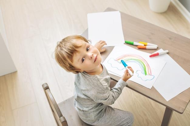 Fröhliches süßes und schönes baby, das zu hause lächelt und am tisch im kinderzimmer zeichnet