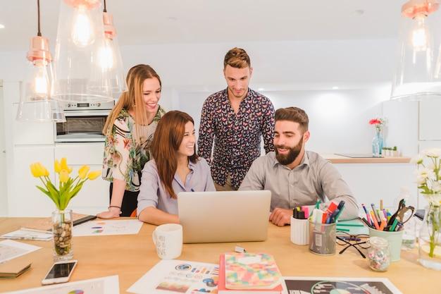 Fröhliches team von arbeitern mit laptop