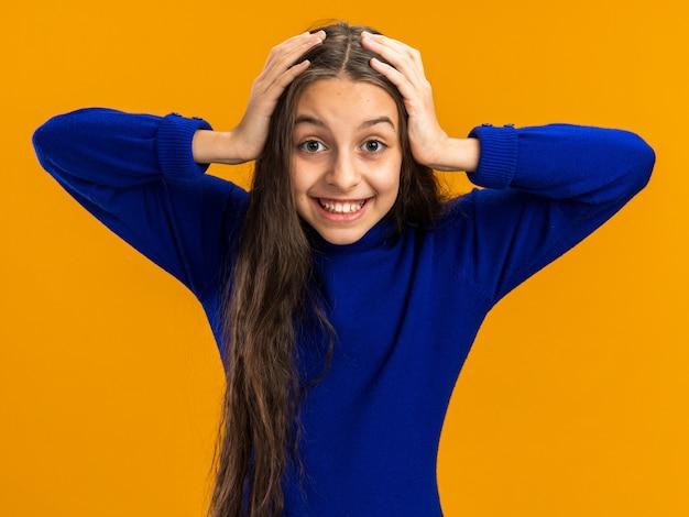 Fröhliches teenager-mädchen, das die hände auf dem kopf hält und nach vorne auf orangefarbene wand schaut?