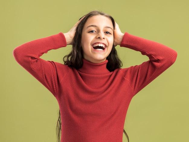 Fröhliches teenager-mädchen, das die hände auf dem kopf hält und nach vorne lacht, isoliert auf olivgrüner wand?
