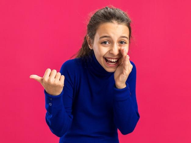 Fröhliches teenager-mädchen, das die kamera anschaut und die hand in der nähe des mundes hält und flüstert, der auf die seite zeigt, die auf einer rosa wand mit kopienraum isoliert ist?