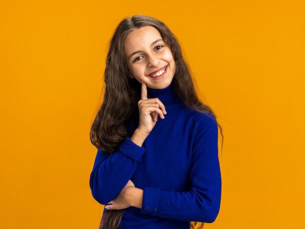 Fröhliches teenager-mädchen, das die kamera anschaut und die wange mit dem finger isoliert auf der orangefarbenen wand mit kopienraum berührt