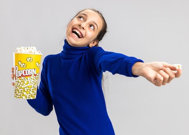Fröhliches teenager-mädchen, das eimer popcorn hält und popcorn-stück in richtung kamera ausstreckt, die isoliert auf weißer wand nach oben schaut