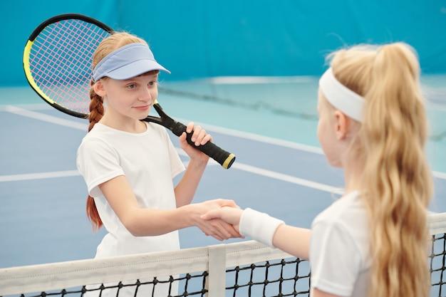 Fröhliches teenager-mädchen in activewear, das tennisschläger hält, während sie die hand ihres freundes über das netz gegen das feld schüttelt, bevor sie im stadion trainieren?