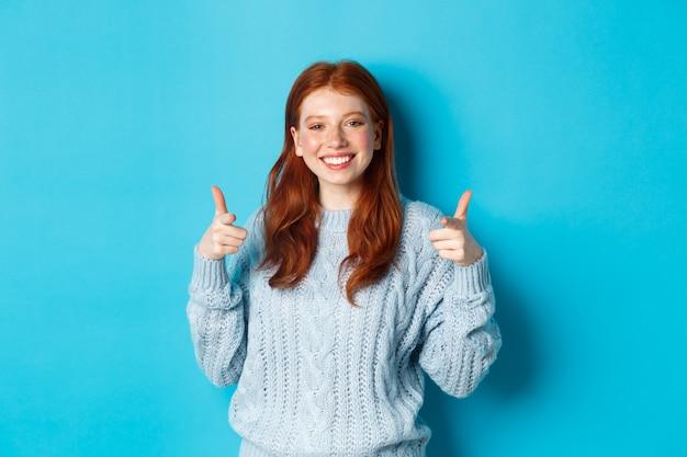 Fröhliches teenager-mädchen mit roten haaren, das mit den fingern auf die kamera zeigt und sie lächelt, gratuliert oder lobt und auf blauem hintergrund steht