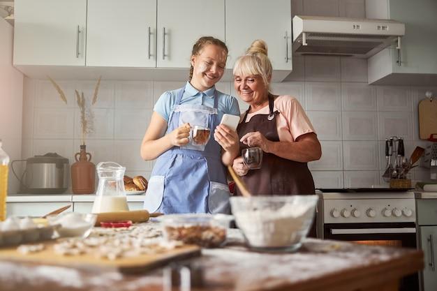 Fröhliches teenager-mädchen und ihre oma genießen gemeinsam teezeit