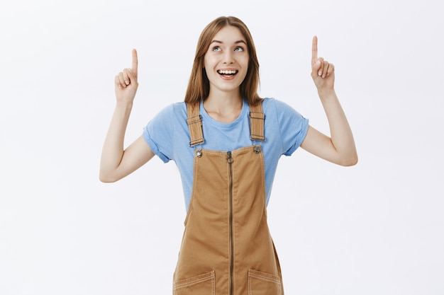 Fröhliches und amüsiertes mädchen, das finger auf logo oder werbung zeigt