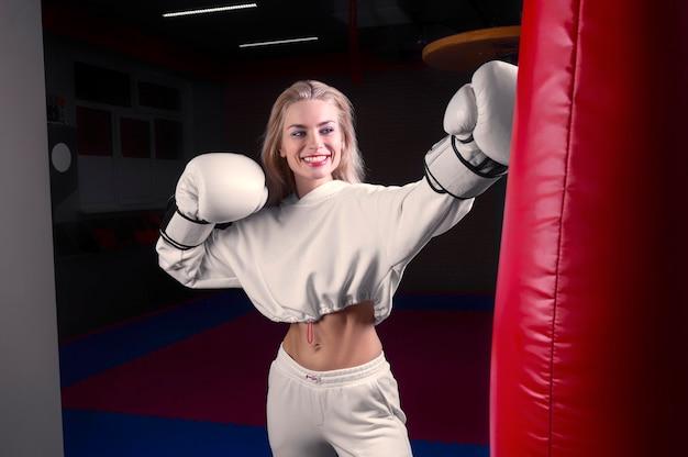 Fröhliches und charmantes mädchen in einem weißen sweatshirt, das in riesigen handschuhen boxt und lächelt. das konzept von sport, fitnessstudios, sportbekleidung, boxen. gesunder lebensstil. gemischte medien