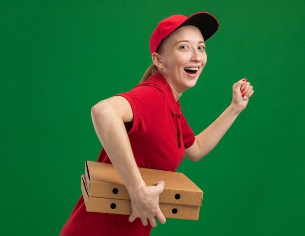 Fröhliches und fröhliches junges liefermädchen in roter uniform und mützenansturm, der für die lieferung von pizzakartons für den kunden läuft