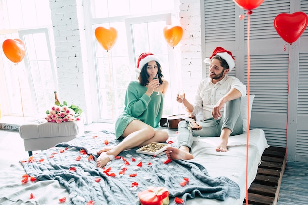 Fröhliches und schönes paar in weihnachtsmützen, die weihnachten feiern