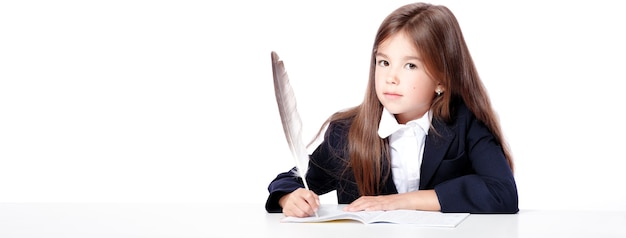 Fröhliches und süßes teenager-schulmädchen schreibt in ein buch oder ein notizbuch